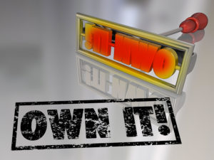 The words Own It on a branding iron to illustrate the concept of